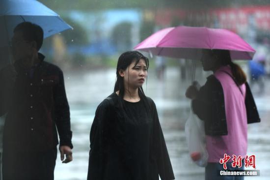 资料图:市民在雨中出行。 陈超 摄