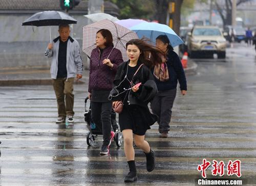 资料图:民众在雨中出行。/p中新社记者 杨可佳 摄