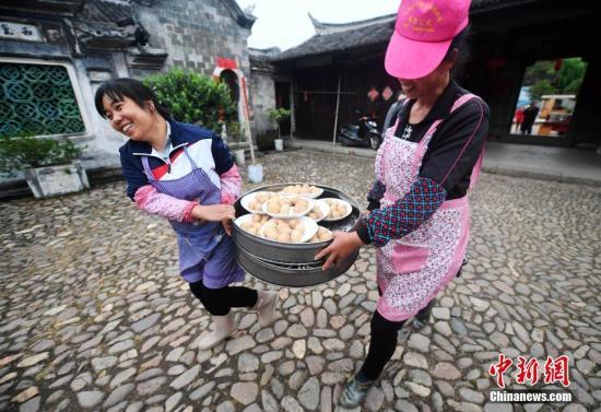 资料图:客家村民将准备好的食物送往宴席处。 张斌 摄
