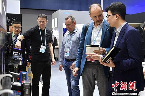 """4月15日,一家电品牌参展商为采购商介绍产品性能。在第123届中国进出口商品交易会(广交会)上,来自34个国家和地区的617家企业在进口展区内展示产品,其中来自21个""""一带一路""""沿线国家和地区的382家企业参展,展位数626个。 <a target='_blank' href='http://www.chinanews.com/'>中新社</a>记者 陈骥�F 摄"""