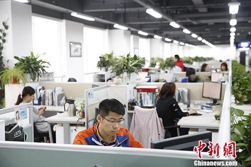 """2014年,北京""""动批""""启动疏解。经过四年时间,2017年11月,""""动批""""内12个市场全部闭市。疏解后的""""动批""""华丽转身。曾经逼仄的摊位,被崭新的现代化办公区取代,一批高科技、文创企业等进驻。""""动批""""也有了新定位——北京金融科技创新示范区。图为4月3日,员工在崭新的现代化办公区工作。中新社记者 韩海丹 摄"""