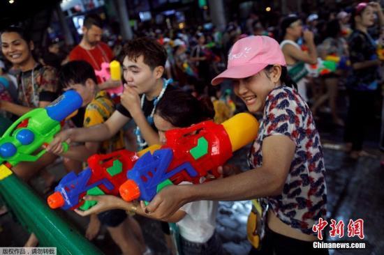 原料图:泰国曼谷街头的游客喜悦地玩水。