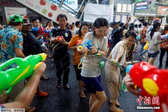 原料图片:曼谷街头的游客喜悦地玩水。