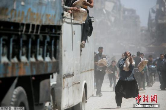 来自美英法的空袭结束,生活还在继续,叙利亚地区派发粮食的车队经过之处,人群紧随其后,分发的大饼被哄抢一空,没有抢到大饼的人只能在地上寻找遗漏的饼渣。