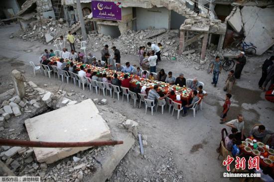 在叙利亚大马士革郊区叛军控制的杜马镇,临近穆斯林斋月结束,当地居民在战场废墟中摆开长桌,享受盛宴。食物主要包含一些传统食品、甜食和饮料等,由慈善组织捐赠。这是当地最好的食物了,也这是孩子们的节日。由于当地没有电力,天黑之后人们就很难看见食物了。