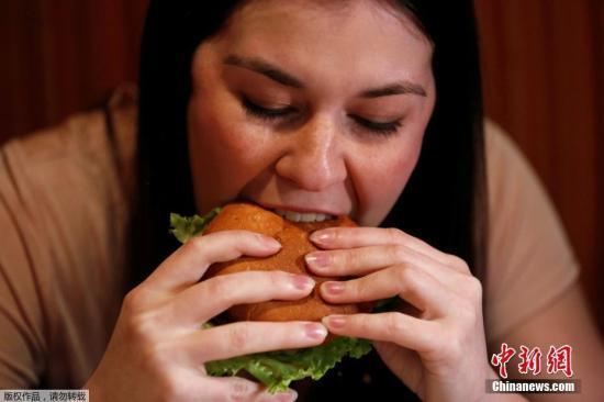 资料图:一名女子正在吃汉堡。