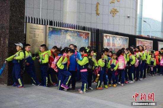资料图:小学生排队等待进入校园。中新社记者 刘文华 摄
