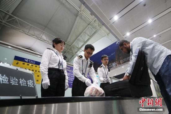 资料图:广州海关隶属广州白云机场海关关员对进境旅客行李进行查验。 <a target='_blank' href='http://www-chinanews-com.monetsalonanddayspa.com/'>中新社</a>记者 池兆恩 摄
