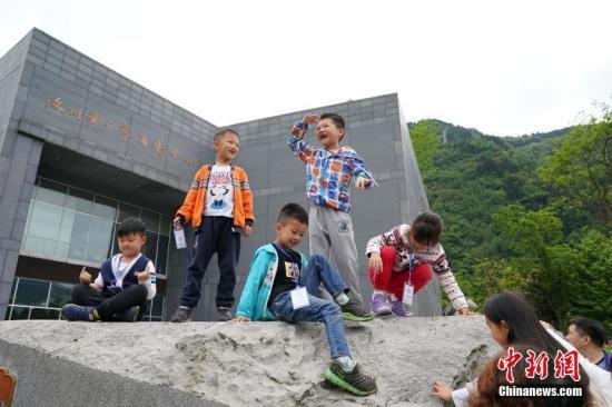 资料图:少年儿童在汶川县映秀镇汶川县青少年活动中心前玩耍。/p中新社记者 毛建军 摄