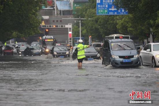 4月22日下午,湖北宜昌突降暴雨,造成市内多路段积水,内涝严重。当地交警、消防紧急出动,确保交通顺畅和民众安全。宜昌市西陵消防中队分组深入内涝区寻找被困人员。截至当日16时30分,消防官兵共疏散50人,救出被困人员6人。图为交警在暴雨中指挥交通。朱华刚 摄