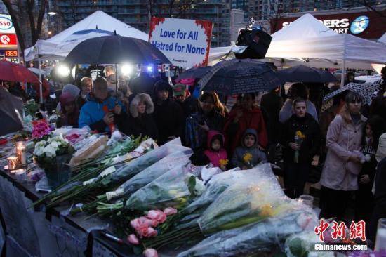 当地时间4月24日,大批加拿大多伦多民众自发来到前一天汽车蓄意冲撞行人案件现场,献上鲜花,点燃烛光,哀悼事件中的遇难者,为伤者祈福。当地时间23日午后,多伦多一繁荣商业区发生汽车冲撞行人恶性案件,现已造成10人罹难、15人受伤。司机已被拘捕。图为民众冒雨前来悼念。/p中新社记者 余瑞冬 摄
