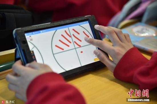 """2018年4月24日,河北省廊坊市一小学,五年级六班的孩子们在""""智慧课堂""""上数学课。该""""智慧课堂""""是利用大数据、云计算、物联网和移动互联网等新一代信息技术打造,实现课前、课中、课后全过程教学应用的智能、高效的课堂。图片来源:东方IC 版权作品 请勿转载"""