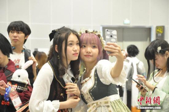 资料图:广西举办中国―东盟动漫游戏展上,精心装扮的动漫爱好者在现场玩起了自拍。钟建珊 摄