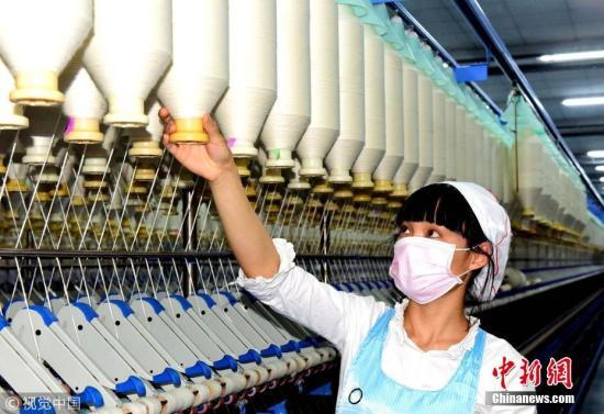 4月28日,江苏怡人化纤纺织有限公司纺纱车间,纺织工人正在生产纱线,满足市场需求。周晓明 摄 图片来源:视觉中国