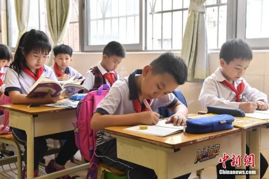 资料图:小学生上课做作业。记者 陈骥�F 摄