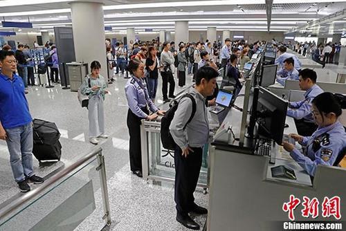 资料图:上海虹桥国际∞机场T1航站楼内入境大厅,民★警正在为旅客办理通关手续。 中新社⌒记者 殷立勤 摄