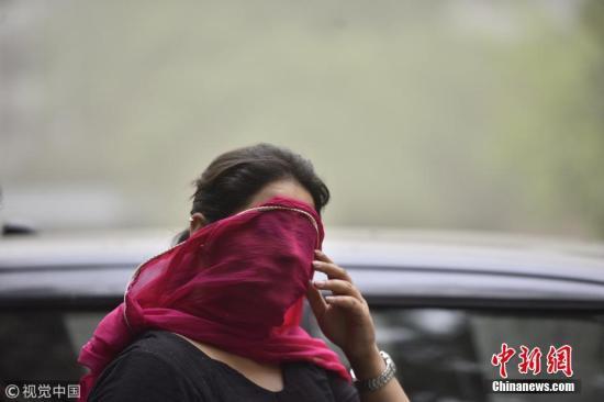 图为当地时间5月2日,印度新德里的一名女子用纱巾遮住脸,躲避沙尘天气的侵扰。 图片来源:视觉中国