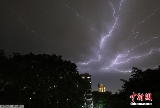 资料图:当地时间5月2日,印度遭受雷暴天气与沙尘暴袭击。图为新德里郊外,天空上布满闪电。