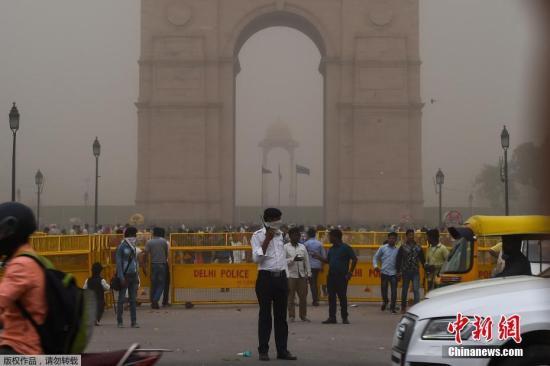 当地时间5月2日,印度新德里的一名交警(中)在沙尘暴天气中带着面巾指挥交通。