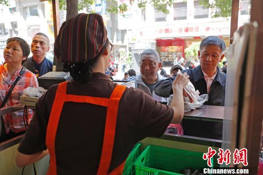 材料图:公众列队购置集拆粽子。 殷坐勤 摄