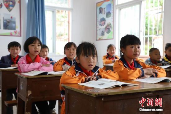 """5月4日,最后一堂课上,学生们认真听讲。贵州省黔西县瓦房村鸭池河岸边的绝壁下,10多栋茅屋零星散落在几乎与世隔绝的深山峡谷里,村民们进出必须翻过一条挂在绝壁上的""""天路"""",而这2公里的路也成了当地10多户孩子最艰难最危险的求学路。为了确保孩子们安全上学,当地小学教师杨绍书担起了守护学生的责任,这一守护就是31年。杨绍书和村里的13户人家5月5日将搬迁到黔西县城,届时他也将完成31年风雨无阻的守护之路。中新社记者 瞿宏伦 摄"""
