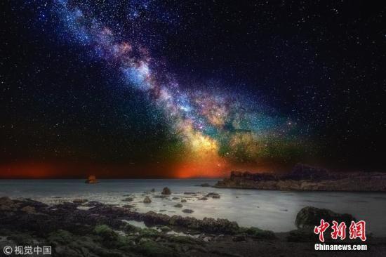 材料图:艳丽的银河及星云与海岸线碰撞出一幅多彩画卷。图片来历:视觉我国