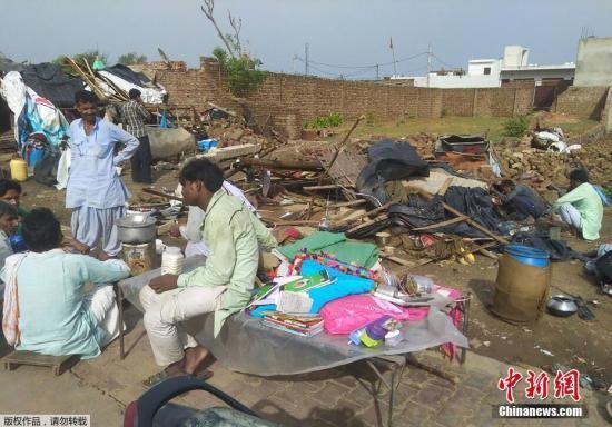 印度每年都会遭遇类似风暴,造成数百人死亡。此次风暴也是数十年来最猛烈的之一。图为5月3日,印度西部拉贾斯坦州婆罗多布尔发生沙尘暴后,人们聚集在被毁的房屋旁。