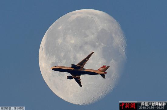 当地时间5月3日,伦敦上空明月高悬,一架英国航空的客机从月亮前飞过。