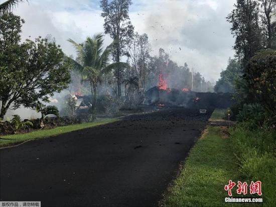 在一个居民约1700人的住宅区,公共工程官员通报路上裂缝冒出蒸气与熔岩后,当局命令居民撤离。夏威夷总共的疏散规模涉及约10000人。图为熔岩从马路上流过。