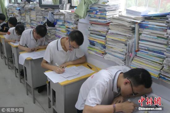 资料图:高三学生在教室内参加高考模拟考试,教室窗台上摆满了各种复习资料。 闫楠 摄 图片来源:视觉中国