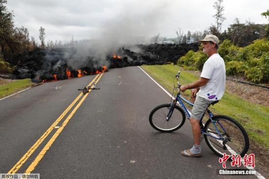 图为一名夏威夷居民骑车行进,前方的道路被熔岩阻断。报道称,火山爆发后,岩浆在火山下流动,大岛4日下午又发生规模6.9级的地震,也是大岛43年来最大的一次地震。