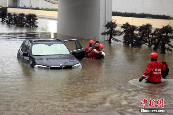 5月7日早上,暴雨致桂林内涝车辆被淹,消防官兵紧急营救出多名被困人员。图为消防员营救两名自驾游北京女子。 中新社记者 阳黎明 摄