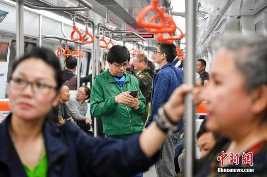 资料图:民众试乘新疆乌鲁木齐地铁1号线。 中新社记者 刘新 摄