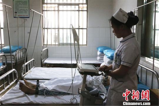 女护士在给精神障碍患者做心电图检查。林馨 摄