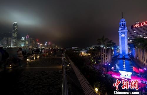 资料图:尖沙咀钟楼蓝色钟楼与维多利亚港的夜景交相辉映。/p中新社记者 张炜 摄