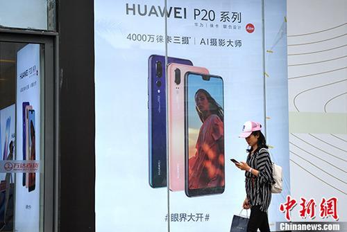 资料图:市民从一国产手机广告旁经过。/p中新社记者 张斌 摄
