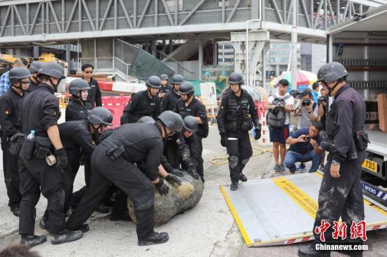 图为拆弹人员正在将已拆除的炸弹装车移走。/p中新社记者 谢光磊 摄