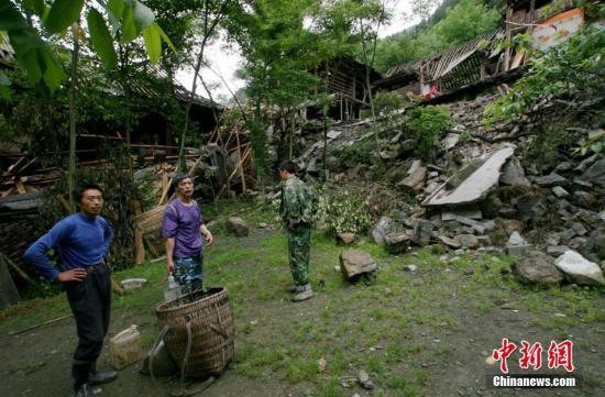 图为2008年5月30日,地震震中附近的人们,左边不远处是倒塌的房屋。 杨建 摄