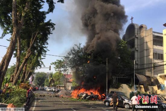 """当地时间5月13日上午,印尼第二大城市泗水的3座教堂接连遭遇炸弹袭击,据印尼国家警察总长迪托将军称,3起爆炸""""造成至少13人死亡,40多人受伤""""。图为泗水市中心的五旬节教堂遭遇炸弹袭击后,附近的摩托车燃起大火。"""