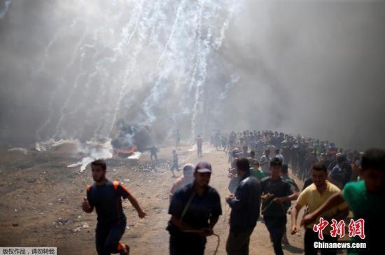 当地时间5月14日,巴勒斯坦民众在巴多地举行游行示威,抗议美国驻以色列使馆当天在耶路撒冷正式开馆。抗议者与以色列士兵发生冲突,导致至少55名巴勒斯坦人死亡、2800多人受伤。图为抗议的巴勒斯坦民众躲避以军发射的催泪弹。