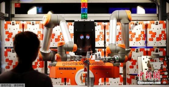 资料图:德国柏林,机器人售货员Gisela组装一个玩具机器人,然后把它卖掉。