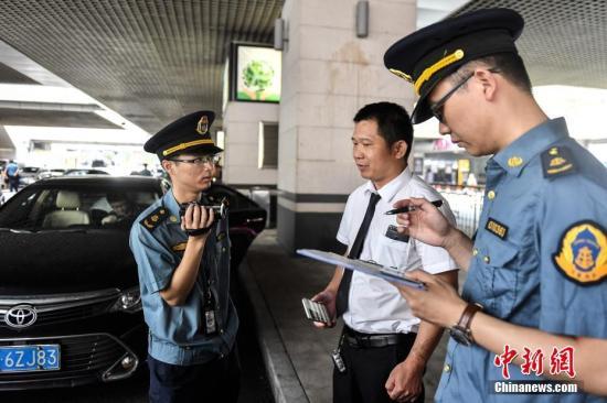 资料图:广州市交通部门开展网约车市场专项整治行动。中新社记者 陈骥�F 摄