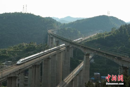 """5月16日,一列动车从贵阳市郊交织的桥梁上驶过。贵州省地处中国西南腹地,高原山地居多,,因此高铁建设的桥隧占比较高。在贵阳市乌当区新添寨,高铁沪昆线、贵广客运专线、贵开城际客运专线的隧道和桥梁交织在一起,形成""""五洞五桥""""并行。/p中新社记者 贺俊怡 摄"""