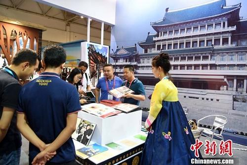 5月18日,21世纪海上丝绸之路博览会暨第二十届海峡两岸经贸交易会在福州开幕,吸引了来自77个国家和地区224个团组共2000余人云集福州。图为客商在朝鲜展位上参观。中新社记者 张斌 摄