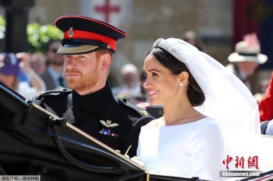 资料图:当地时间5月19日,英国哈里王子与美国女星梅根・马克尔在英国温莎城堡举办婚礼。新人乘坐马车亮相。