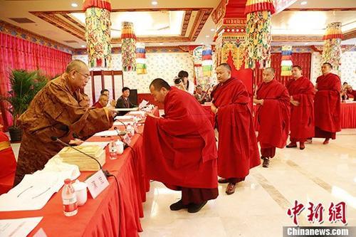 """5月19日,藏传佛教第十四届""""拓然巴""""高级学衔授予仪式在中国藏语系高级佛学院举行,来自藏传佛教格鲁派和萨迦派的20名学僧,经过三年学习,通过课程考核、论文答辩、辩经考试和资格审查,喜获""""拓然巴""""高级学衔。中央统战部和中国佛教协会有关负责人出席学衔授予仪式并致辞。中国佛教协会副会长、中国藏语系高级佛学院院长嘉木样・洛桑久美・图丹却吉尼玛活佛向""""拓然巴""""高级学衔获得者颁发证书。 <a target='_blank' href='http://www.chinanews.com/'>中新社</a>记者 刘关关 摄"""