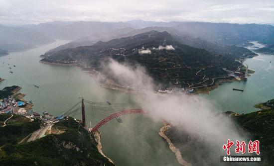 5月22日,世界最大跨度钢箱桁架推力式拱桥――香溪长江大桥主拱成功合龙。该桥是三峡后续规划项目,位于三峡库区湖北省秭归县境内,桥身全长883.2米,主跨531.2米,为一跨过江、双向四车道公路桥。项目建成后将打通沪蓉、沪渝高速,串起三峡、神农架、武当山三大世界级景点,打破秭归县长江两岸以汽渡为唯一通道的交通现状。图为雨雾中的香溪长江大桥。 <a target='_blank' href='http://www.chinanews.com/'>中新社</a>记者 郑家裕 摄
