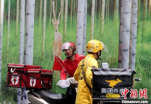 资料图:北京西单街头的外卖骑手准备送餐。 <a target='_blank' href='http://www.chinanews.com/'>中新社</a>记者 张宇 摄