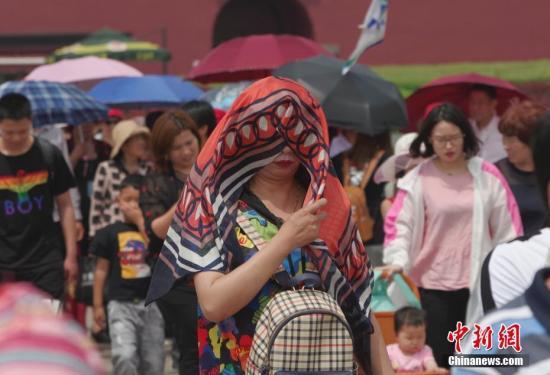 5月25日,北京炎热高温天气持续,天安门前一位游客把纱巾盖在头上防晒。 <a target='_blank' href='http://www.chinanews.com/'>中新社</a>记者 贾天勇 摄