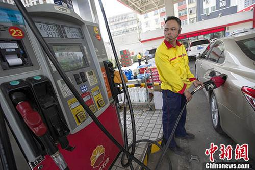5月25日,山西太原,加油站工作人员正在加油。当日,中国国家发改委网站公布消息称,根据近期国际市场油价变化情况,按照现行成品油价格形成机制,自2018年5月25日24时起,中国国内汽、柴油价格(标准品,下同)每吨分别提高260元和250元。至此,中国国内成品油价格迎来2018年以来的第七次上调,且创下年内最大涨幅。 <a target='_blank' href='http://www.chinanews.com/'>中新社</a>记者 张云 摄